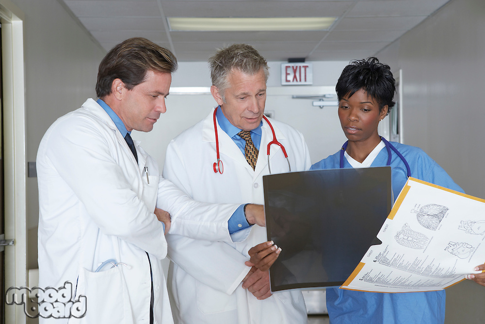 Medical personnel looking at x-ray image in hospital hallway