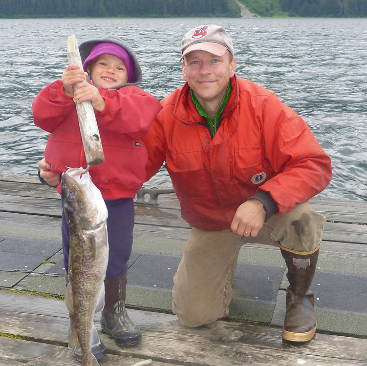 A father and son pose with the boy's catch of a large cod in Excurision Inlet.