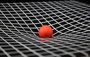 A simulation of gravity showing curved space-time.  The ball represents the sun and is resting on a sheet of plastic that stretches under its weight.  The curved sheet of plastic is a way to visualize the way a gravity curves space.