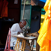 India. Bihar. Bodhgaya, the town where the Buddha sat under a sacred fig tree (bhodi tree) and received enlightenment. Tailor at work.