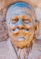 Close-up of a bas relief portrait of a jolly man on a grave in Isola San Michel in Venice, Italy.