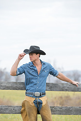 All American cowboy in chaps leaning against a rustic wooden fence on a ranch