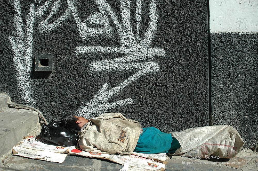 Boy sleeping on the sidewalk in La Paz, Bolivia