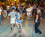 """People dance the Chamamé at a free public dance in Dorrego Square, in San Telmo barrio of Buenos Aires, Argentina, South America. Chamamé is a folk music genre from northeast Argentine (""""Litoral,"""" including La Mesopotamia, Región Mesopotámica) and southern Brazil. Accordion-based Chamamé arose in Corrientes Province, an area with many immigrants from Poland, Austria, and Germany (many of them Jews), who brought Polkas, Mazurkas and Waltzes which mixed with local Spanish music."""