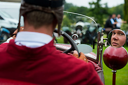 © Licensed to London News Pictures. 13/07/2015. Epsom, UK. A race competitor prepares to set off by checking his mirrors. The start of The Royal Automobile Club 1000 Mile Trial 2015 at Woodcote Park in Epsom, Surrey. The event, which starts and finishes at Woodcote Park, takes a fleet of over 40 classic cars from around the world, through a 1000 mile trial around the UK.  Photo credit: Ben Cawthra/LNP