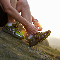 A photograph of a fell runner tying his shoelaces on a rock on Ilkley Moor at sunset