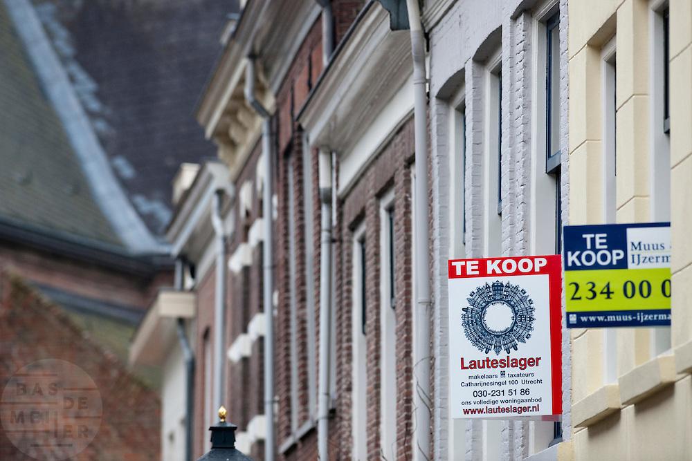 Borden aan de gevels geven aan dat huizen te koop staan in Utrecht.