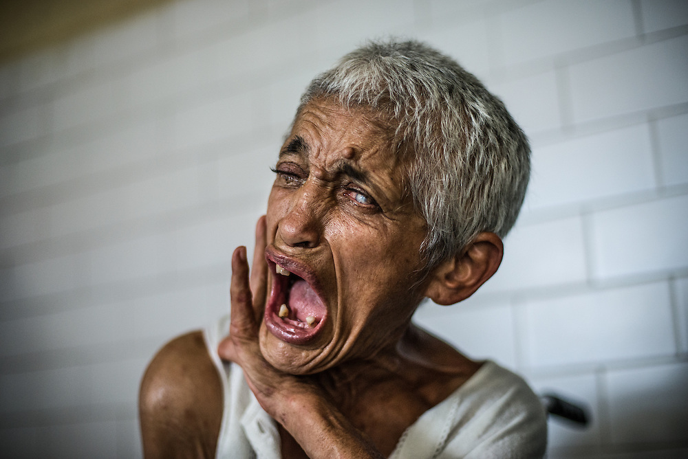 """BARQUISIMETO, VENEZUELA - JULY 28, 2016: Emiliana Rodríguez screams at the top of her lungs over and over again, """"I'm NOT crazy, I'm just HUNGRY!""""  Mrs.Rodríguez is a hospitalized schizophrenic who doctors say functioned well when she had medication, but that she has sunk into a delusional state and can no longer even walk, confined to a broken wheel. She currently only receives two of the six medications she was prescribed. The other 4 cannot be found because of shortages. """"The disease has taken her over,"""" said Évila García, the chief nurse. There is also no medication for her glaucoma which staff said had left her hardly able to see. PHOTO: Meridith Kohut"""