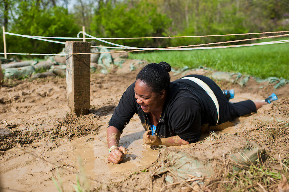 Kateri Dover of Marietta, OH, crawls through the mud at the old Army ROTC training course located at the Ridges during the O'Bleness Race for a Reason Mud Run, Saturday, April 27, 2013. The course included a four-mile run up to the old Army ROTC Course at the Ridges, through the Radar Hill Trail and back to Tail Great Park across from Peden Stadium. Race for a Reason, Race 4 A Reason, Annual Events, Events, Students, Faculty & Staff