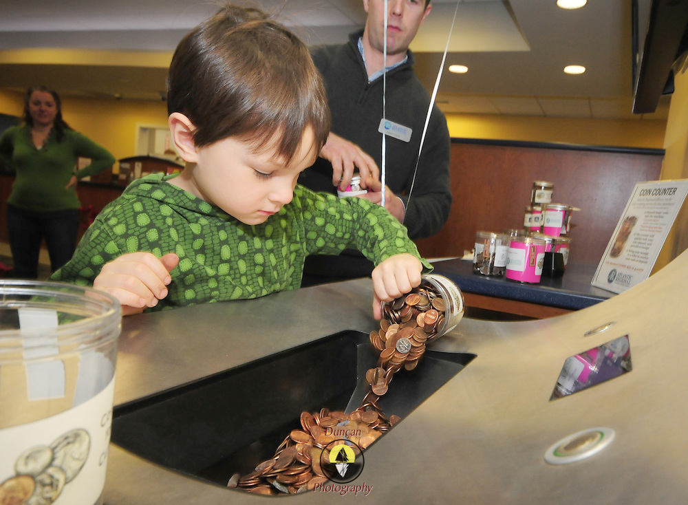 BRUNSWICK, Maine -- Oliver Casey, age 5 and a half, of Brunswick, helps the staff at Atlantic Regional Federal Credit Union with pouring fundraised coins into the coin counter at the Brunswick branch. The credit union and Gelato Fiasco combined to create a Curtis Memorial Library Fundraiser in which kids used empty gelato jars as coin collectors in February -- as part of national Love your Library month. Casey estimated that there would be a million dollars in the collections - but after all the change was counted, the total came close to one thousand dollars. Photo by Roger S. Duncan for The Forecaster.