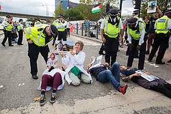 London, UK. 2 September, 2019. Police officers remove from the road outside ExCel London activists holding images of Palestinians killed by Israeli attacks on Gaza on the first day of week-long protests against DSEI 2019, the world's largest arms fair. The first day of creative action was hosted by activists calling for a ban on arms exports to Israel and featured workshops, speakers, street theatre and dance. Israeli arms companies display weapons at DSEI marketed as 'combat-proven' following deployment against Palestinian communities.