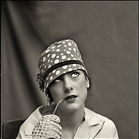 A teenage girl wearing a spotty hat and gloves