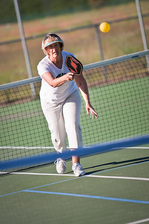 Judy Thormahlen of Hayden sends a serve to her competitors Thursday evening on the tennis courts at Northshire Park.