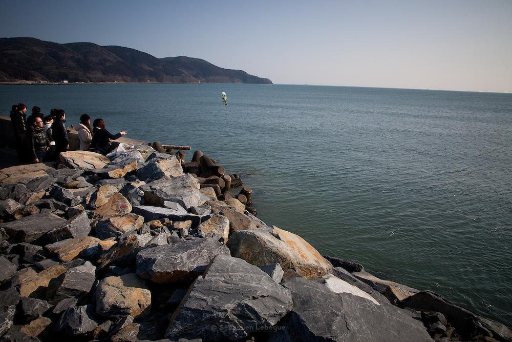 Ishinomaki  Offrande de fleur à la mer  11 mars 2012 14:46.Le 11 mars 2012 à 14h46, un an après le séisme, la sirène retentit dans la ville. Tout le japon est à larrêt pour une minute commémorative. Sur la barrière anti-tsunami, les familles se regroupent pour une prière face à la mer. Les fleurs sont lancées à leau ou déposées sur les rochers. De lencens est brulé.