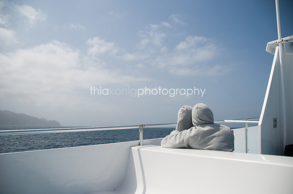 Two people in grey hoodies snuggle on the cold ferry ride from Catalina back to the mainland of California.