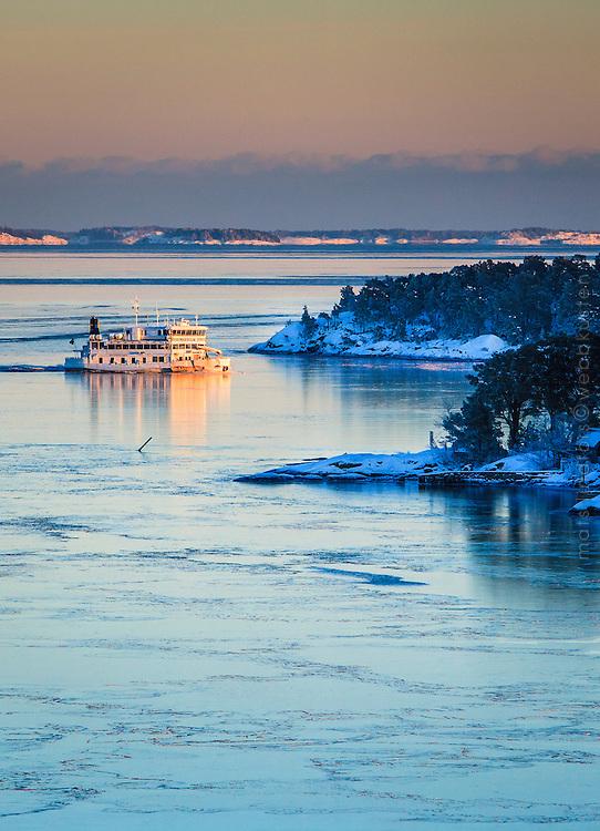 Vinter snö och is och en Waxholmsbåt vid Jungfrufjärden i Stockholms skärgård