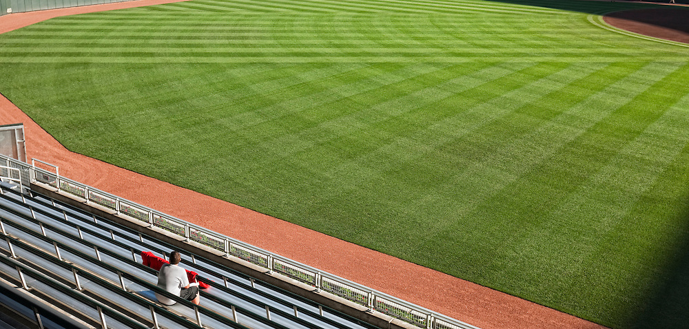 Single fan sits in the bleachers very early, eagerly waiting for the upcoming ball game.