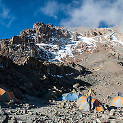 Tents set up at Arrow Glacier Camp (15,970 feet) with the Western Breach and summit behind them on Mt Kilimanjaro's Lemosho Route.