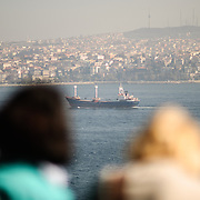 The view of shipping on the Bosphorus from the Topkapi Palace with tourists in the foreground.