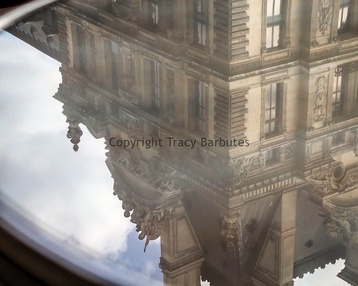 The Louvre Museum is reflected in a cafe table in Paris, France