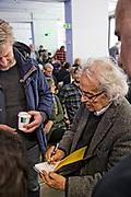 Adonis skriver autograf i boka til Petter Kjørstad fra Trondheim. Den syriske poeten Adonis (86),  hovedgjest under Æ Å Trondheim Litteraturfestival i mars 2017. Den 86 år gamle forfatteren og poeten Ali Ahmad Said er mannen bak kunstnernavnet Adonis, og han har i hele sin lange karriere stilt spørsmål rundt poesi, politikk og religion. Her i samtale med Litteraturhusets leder Trond Åm bl.a.  med utgangspunkt i Adonis`bok «Vold og Islam», som kom på norsk i 2016. En bok han har fått mye oppmerksomhet for, men også har møtt mye motstand mot. Adonis snakket på fransk og brukte tolk. Adonis (Ali Ahmad Said Esber) is a Syrian poet, essayist and translator who is considered one of the most influential and dominant Arab poets of the modern era. Adonis's publications include twenty volumes of poetry and thirteen of criticism, and dozen books of translation to Arabic. Islamic authorities and scholars have opposed Adonis for his criticism of Islam. Some, such as Egyptian Salafi Mohamad Said Raslan and some faction of the Syrian opposition, issued death threats against him, and some called for his books to be burned. In spite of this opposition, Adonis is a perennial contender for the Nobel Prize in Literature, Adonis has been described as the greatest living poet of the Arab world. Born to a modest Alawite farming family[8] in January 1930, Adonis hails from the village of al-Qassabin near the city of Latakia in western Syria. He was unable to afford formal schooling for most of his childhood, and his early education consisted of learning the Quran in the local kuttab (mosque-affiliated school) and memorizing classical Arabic poetry, to which his father had introduced him.