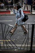 Woman pedestrian walks past bent railings in a London street.