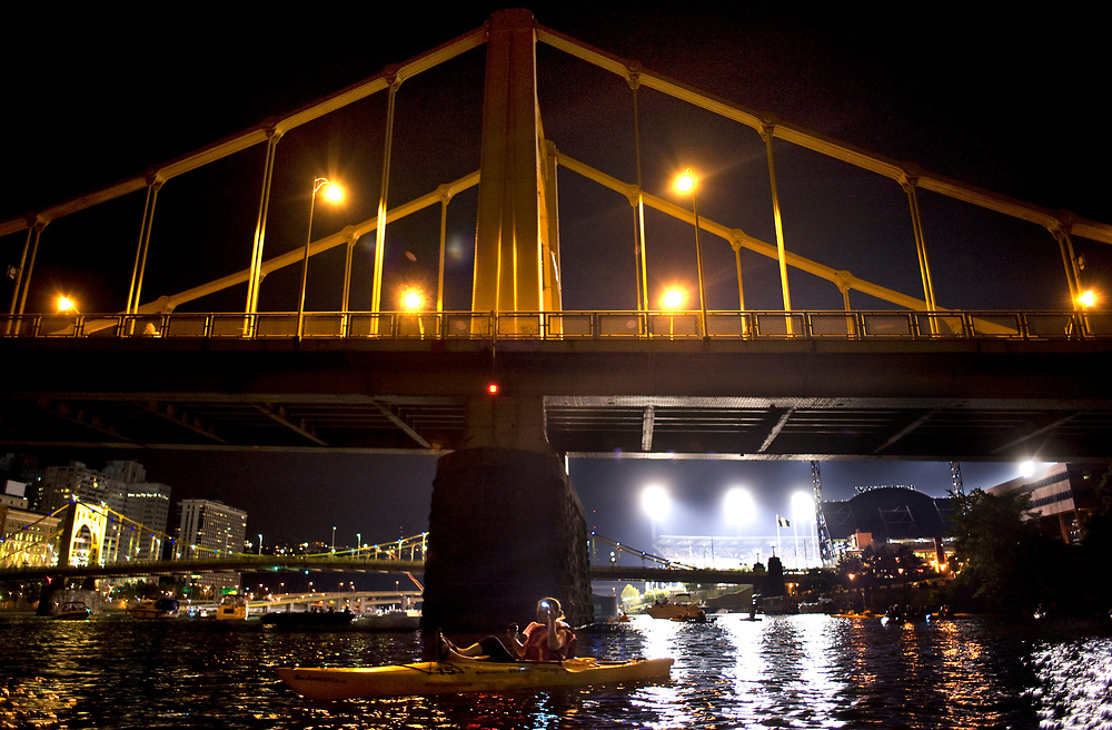 A kayaker relaxes near the 7th Street Bridge in the Allegheny River in Pittsburgh before the fireworks to begin while participating in Venture Outdoors' Fireworks Paddle.