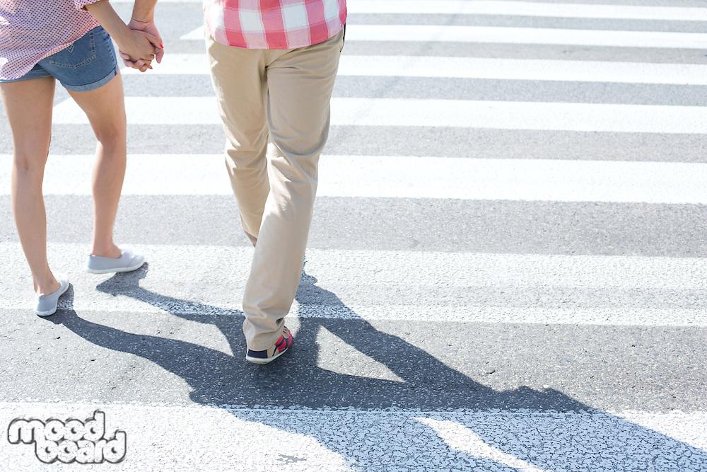 Low section of couple walking on crosswalk