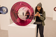 New York, NY - May 3, 2019. A woman having fun with Fred Eversley's untitled cast polyester pieces at the David Kordonskky Gallery at the Frieze Art Fair on New York City's Randalls Island.