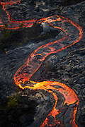 A river of molten pahoehoe snakes its way through an area that had been ravaged by lava 10 years ago, consuming vegetation that was just beginning to establish itself, as the flow front advances toward the sea.