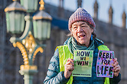 A lady passionately shouts out answers to a questionaire. Westminster Bridge is the first blocked - Extinction Rebellion Day -  co hosted by Rising Up, 'Rebel Against the British Government For Criminal Inaction in the Face of Climate Change Catastrophe and Ecological Collapse'. A protest that involves blocking 5 bridges: Southwark, Blackfriars, Waterloo, Westminster and Lambeth.
