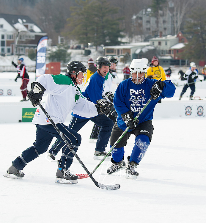 John Hanaway of Re/Max Hackers and Joe Spicuzza of the Puck Nuts battle for the puck during first round action at Meredith Bay during the New England Pond Hockey Classic Friday morning.  (Karen Bobotas/for the Laconia Daily Sun)