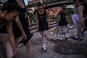Students of the Manguinhos community ballet dress their shoes after posing for portraits aside a commercial railroad that crosses their impoverished neighbourhood   in Manguinhos neighbourhood in Rio de Janeiro, Brazil, Monday, June 11, 2018. The Manguinhos community ballet has been a reprieve from the violence and poverty that afflicts its namesake neighborhood for hundreds of girls who have benefitted from free dance classes since 2012. (Dado Galdieri for The New York Times)