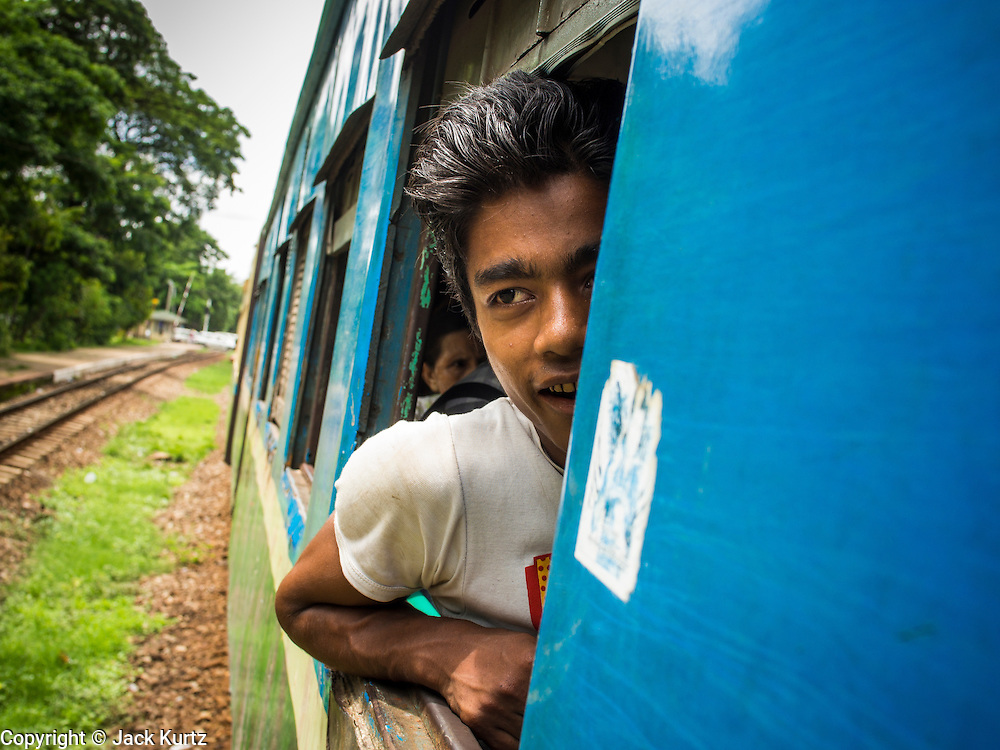 05 JUNE 2014 - YANGON, YANGON REGION, MYANMAR: A passenger of the Yangon Circular Train. The Yangon Circular Train is a commuter train that circles Yangon, Myanmar (Rangoon, Burma). The train is 45 kilometers long, makes 38 stops and takes about three hours to make a loop of the city.     PHOTO BY JACK KURTZ