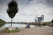 Een man op een scootmobiel rijdt langs de Maashaven in Roermond met in de achtergrond het terrein van de Kalle en Bakker Betoncentrale. <br /> <br /> A man on a scooter drives along the Maashaven in Roermond in the background field of Kalle and Baker Concrete plant.