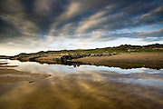 Skies reflected in the mirror-flat river which flows down to the main beach at Rhosneigr, West Anglesey.