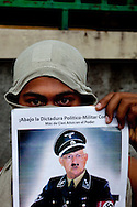 A protestor holds a photo depicting current President Micheletti in a march supporting President Zelaya in Tegucigalpa on July 3, 2009. Zelaya is supposed to return this weekend, however the current government has promised to put him in jail if he enters the country.