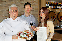 Portrait of happy young couple with chef holding pizza