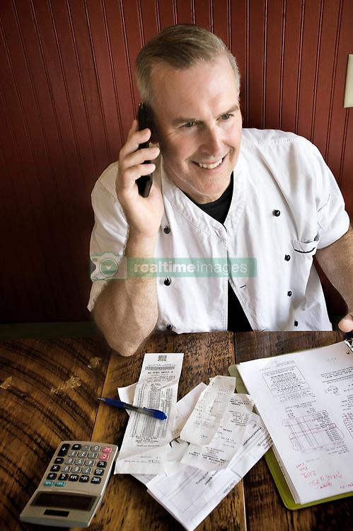 July 6, 2016 - ''Chef working on accounts, using cellphone' (Credit Image: © Leland Bobbe/Image Source via ZUMA Press)