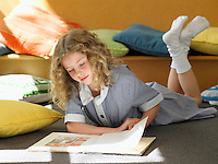 Elementary schoolgirl reading book lying on stomach on floor