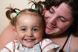 Close portrait of a happy young mother holding her baby,