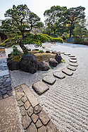 A wealthy landowner, Genji Tanaka donated the space for Edogawa Gyosen Garden to the city of Tokyo City, Edogawa ward in 1950.  They created Gyosen Park as we see it today. Its Heisei Garden was created in 1989, with a pond side tea house Genshinan which can be rented out for tea ceremony and special occasions. A stone pathway encircles the pond in the Heisei Garden, passing among craggy rocks that one has to climb over.  In flatter terrain, behind Genshinan Teahouse, there is a fine large dry karesansui garden, rarely visited by park goers.