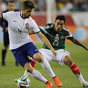 Miguel Veloso, (left), Portugal, challenged by José Vázquez, Mexico, during the Portugal V Mexico International Friendly match in preparation for the 2014 FIFA World Cup in Brazil. Gillette Stadium, Boston (Foxborough), Massachusetts, USA. 6th June 2014. Photo Tim Clayton