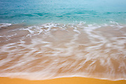 Pacific Ocean waves flow over the golden sand at Napili Beach, located on the west side of the Hawaiian island of Maui.
