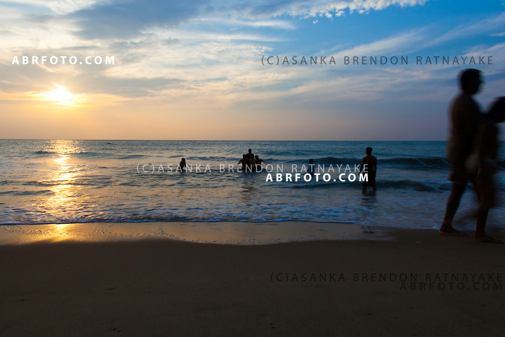 The sunsets on the beach of Negombo as beachgoers play. Negombo is a major city in Sri Lanka, located on the west coast of the island and at the mouth of the Negombo Lagoon