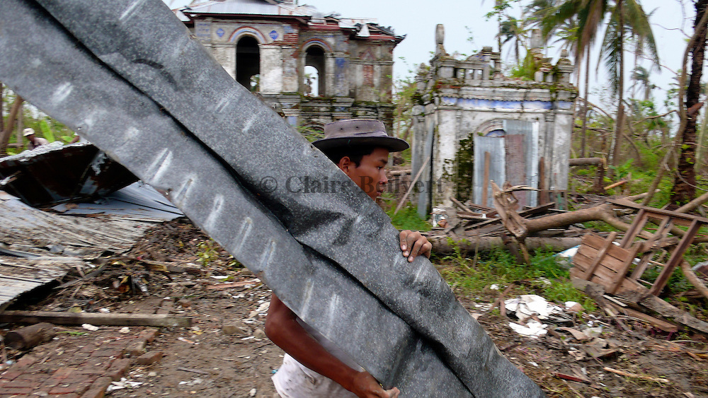 Young man trying to move away the roof of the monastery that had collapsed during Cyclone Nargis. Around two hundred villagers who were taking refuge in the temple died when it collapsed.