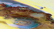 This prominent circular feature, known as the Richat Structure, in the Sahara desert of Mauritania is often noted by astronauts because it forms a conspicuous 50-kilometer-wide (30-mile-wide) bull's-eye on the otherwise rather featureless expanse of the desert. Initially mistaken for a possible impact crater, it is now known to be an eroded circular anticline (structural dome) of layered sedimentary rocks. This view was generated from a Landsat satellite image draped over an elevation model produced by the Shuttle Radar Topography Mission (SRTM).  taken in 2000.