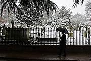 Man with umbrella walks past snow covered graveyard, Hampstead, London, United Kingdom