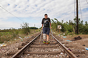 Hassan Hassanein, 14, makes his way on crutches as he crosses into Hungary from Serbia on an abandoned railway line used by mostly Syrian refugees. Refugees at Roszke Crossing on Serbian-Hungarian Border.