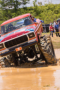 A monster truck outfitted with special tires rides through a pool of mud during the Mudding Event at the 2015 National Red Neck Championships May 2, 2015 in Augusta, Georgia. Hundreds of people joined in a day of country sport and activities.